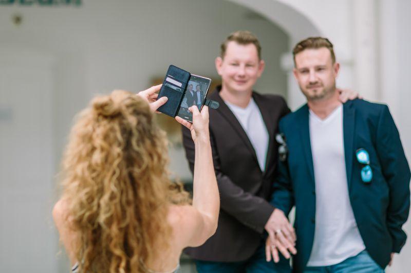 hochzeitsfotograf kaernten, bojan und roman, ein gleichgeschlechtliches paar nach der verpartnerung im standesamt in feldkirchen werden von der schwester fotografiert mit dem iphone
