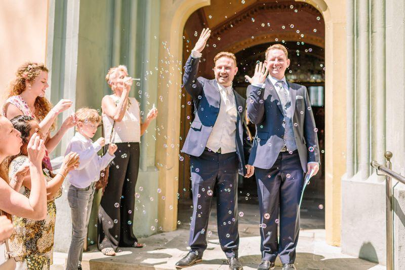 hochzeitsfotograf kaernten, bojan und roman, ein gleichgeschlechtliches paar beim Auszug nach der trauung in der johanneskirchein klagenfurt